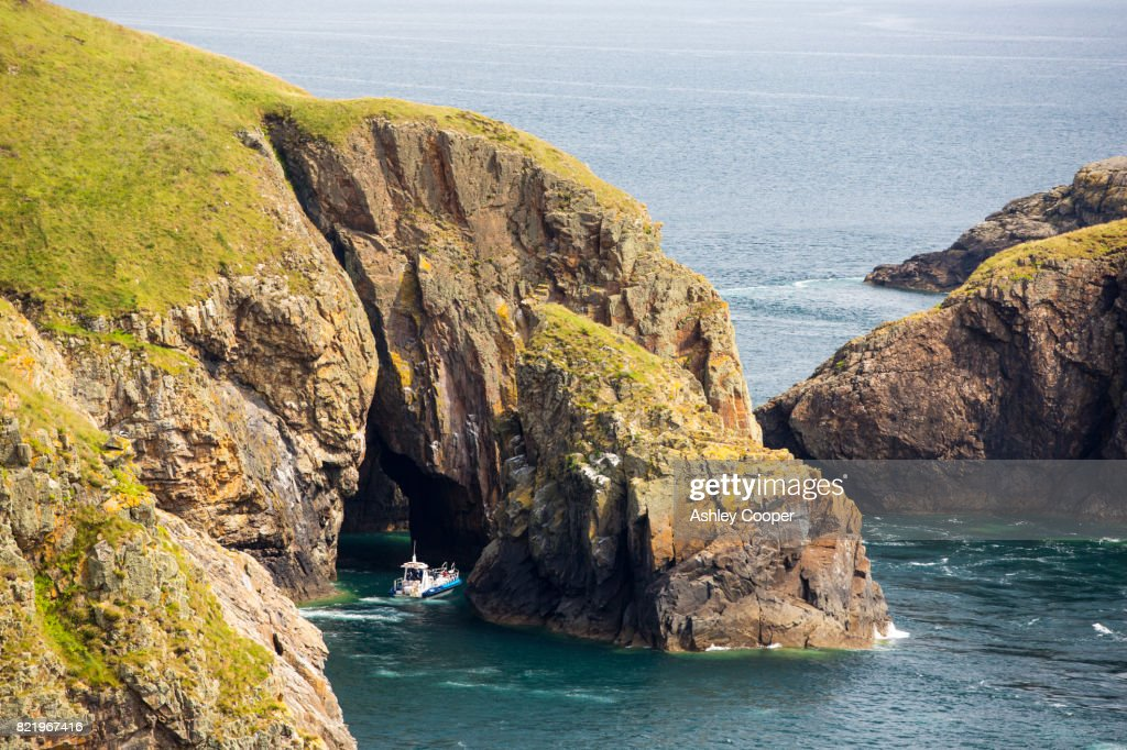 Looking towards Yns Cantwr off the southern tip of Ramsey Island, Pembrokeshire, Wales, UK, with a tourist boat entering a sea cave. : Stock Photo