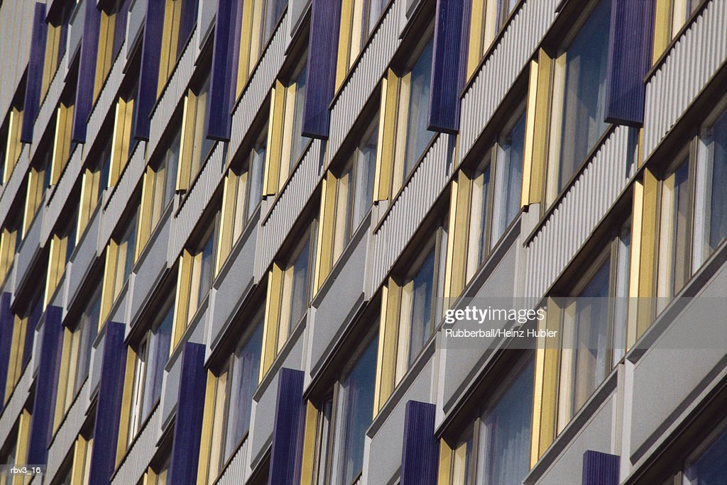 looking up a business wall covered with windows sided with yellow and white material : Foto de stock