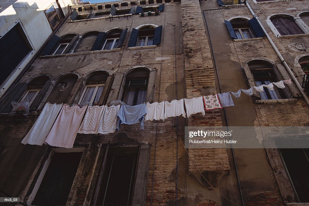 looking up a wall of an old European brick apartment with a clothes line and laundry draped across it : Stockfoto