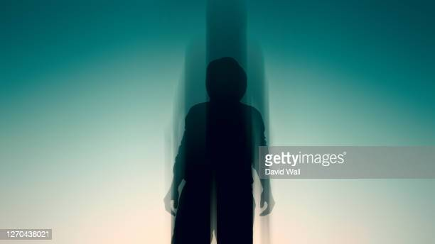 looking up at a mysterious hooded figure, silhouetted by the sun. with a blurred, out of focus edit. - in silhouette stock pictures, royalty-free photos & images