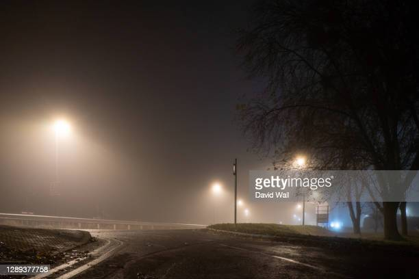 looking up at a road and street lights on an atmospheric foggy winters night. uk. - town stock pictures, royalty-free photos & images