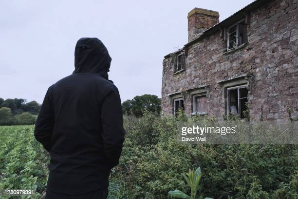 looking up at a spooky abandoned house, with a hooded figure, back to camera. standing in the countryside - abandoned stock pictures, royalty-free photos & images