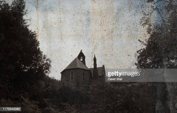 looking up at a spooky church surrounded by trees in the countryside with a moody, vintage, grunge edit. - church stock pictures, royalty-free photos & images