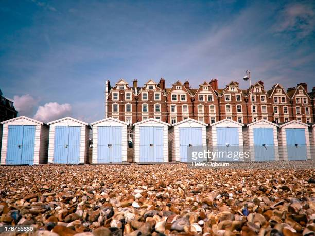 Looking up at eight white beach huts with closed blue doors on a shingle beach on a sunny day. Behind the beach huts are a row of terraced...