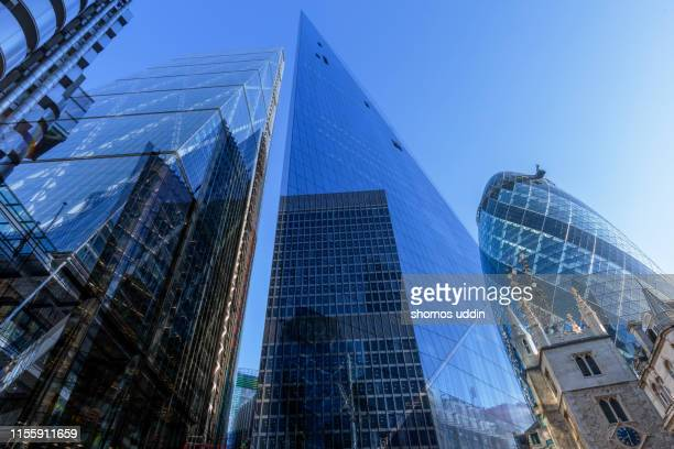 looking up at futuristic office buildings - glass material stock pictures, royalty-free photos & images