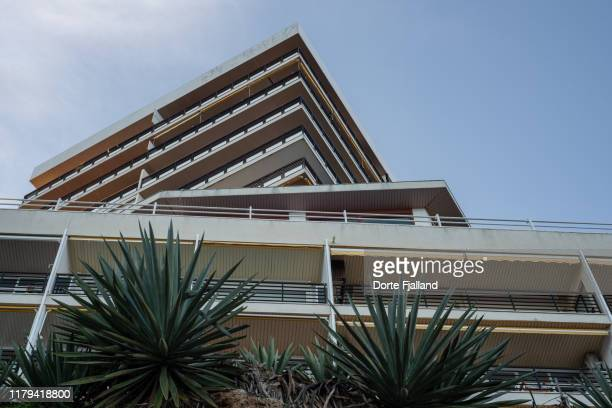 looking up at one white concrete building with another building above it in a different angle against a blue sky - dorte fjalland stock pictures, royalty-free photos & images
