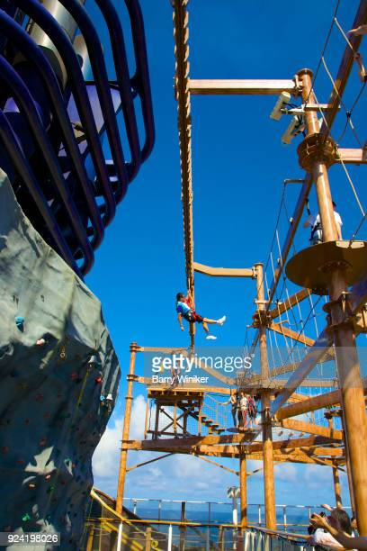Looking up at people on zip line, near ropes course and climbing wall on cruise ship