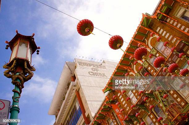 Looking up at red Chinese lanterns and buildings
