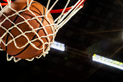 Looking up at the bottom of a basketball falling through the net with arena lights in the background 1135431819