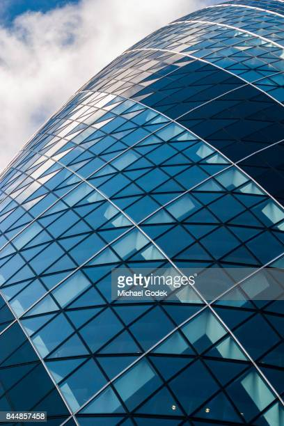 Looking up at the famous Gherkin building in London's Financial district against a cloudy blue sky