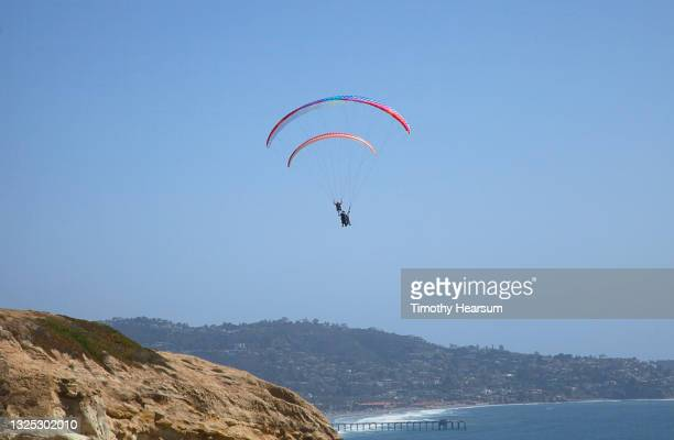 looking up at two paragliders; cliff, ocean and pier in foreground; coastline and blue sky beyond - timothy hearsum fotografías e imágenes de stock