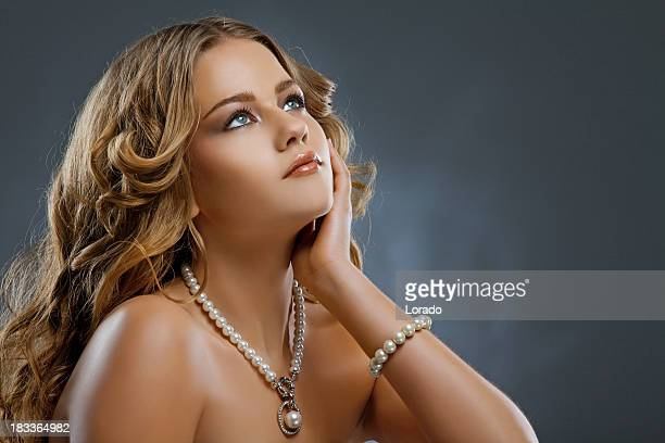 looking up beautiful woman wearing pearls necklace