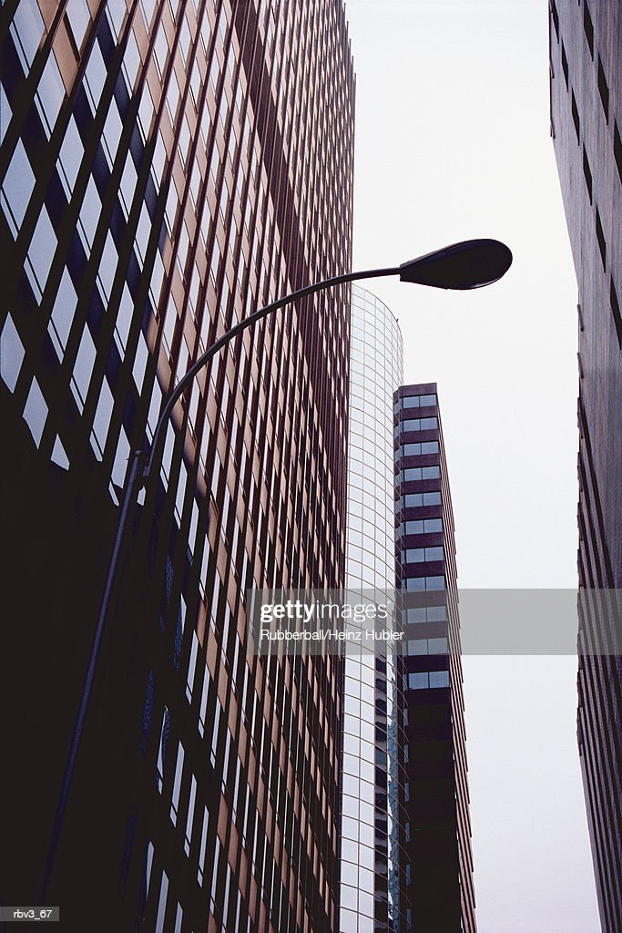 looking up between large skyscrapers to see glass windows and a street lamp and a white sky : Foto de stock