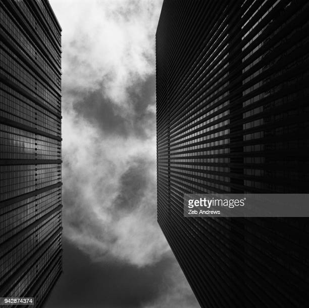 looking up between skyscrapers - moody sky stock pictures, royalty-free photos & images