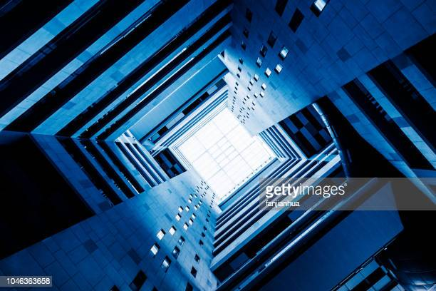 looking up from the atrium of a highrise building - diminishing perspective stock pictures, royalty-free photos & images