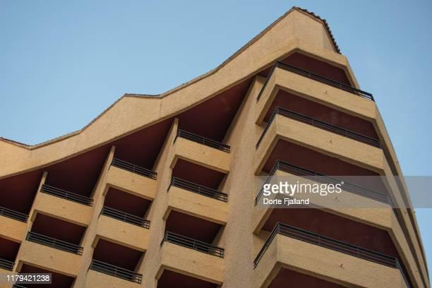 looking up on a yellow facade with balconies and a blue sky at the top - dorte fjalland fotografías e imágenes de stock