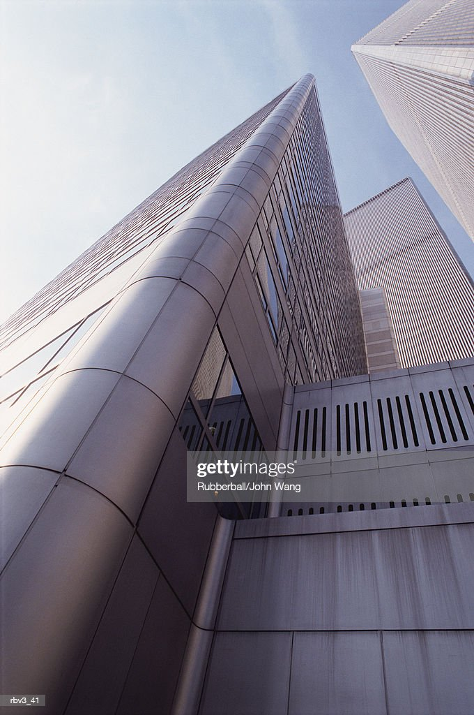 looking up the side of a silver gray building with reflective windows leading to the blue sky with white clouds : Stockfoto