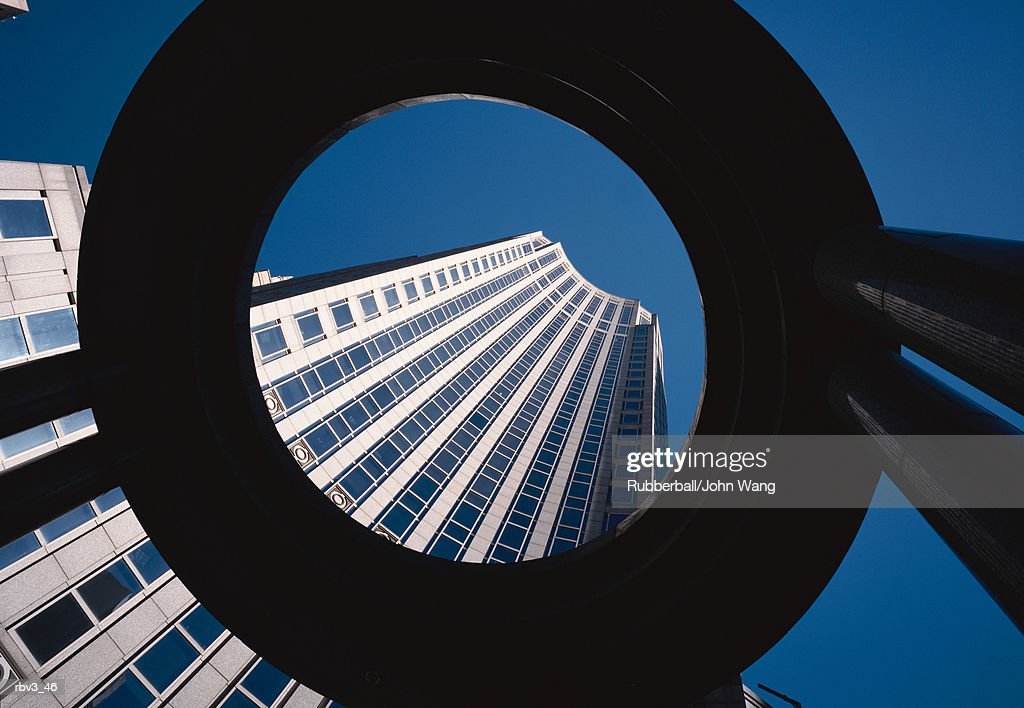 looking up through a large black circle to see a curved building with large black windows reaching toward the clear blue sky : Foto de stock