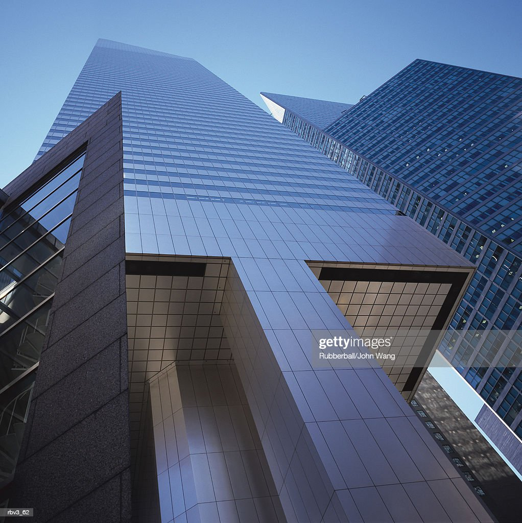 looking up to see a modern gray building with black windows reaching to a blue sky : Foto de stock