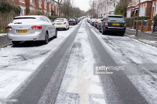 Looking uphill, an urban landscape scene of a light dusting of snow that has covered the road surface of a residential street in Herne Hill, SE24,...