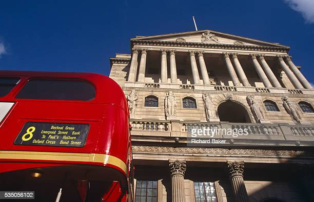 Looking upwards towards the back of a number 8 red London bus which passes the pillars of the famous Bank of England building at Cornhill in the City...