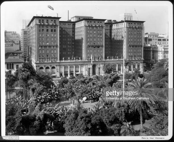 Looking west over the palms and banana trees of Pershing Square to the Biltmore Hotel which opened in 1923 Los Angeles California early to mid...