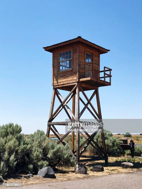 lookout tower on land against clear blue sky - lookout tower stock pictures, royalty-free photos & images
