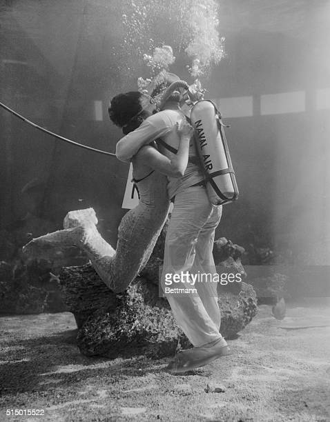 Looks as if the water is boiling over the heads of Navy parachute rigger 2nd class W. Donaldson and pretty mermaid, Betty Connell as they go into a...