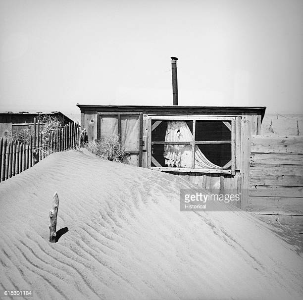 Loose soil, blown by dust bowl winds, piled up in front of an outhouse on a farm. Cimarron County, Oklahoma, April 1936.