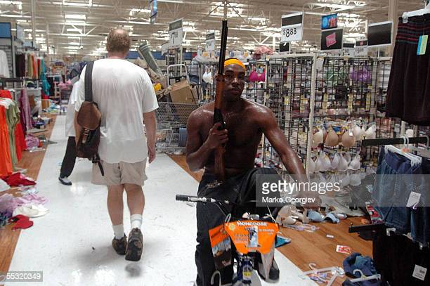 A looter caries a rifle while riding a bike in a KMart in the Garden District in New Orleans Louisiana on August 30 2005 after Hurricane Katrina...