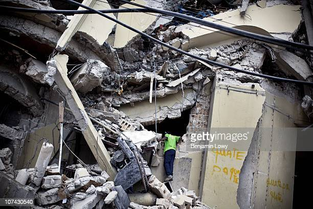 Looter climbs into the unstable remains of the Caribbean Market in Port au Prince on February 10 2010. Haiti was struck by a magnitude 7 earthquake...
