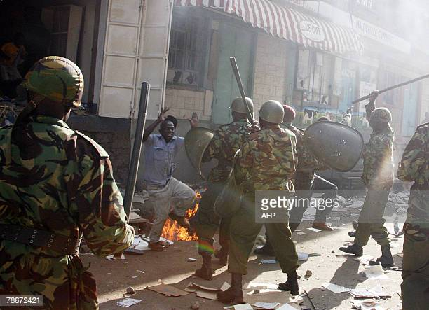 A looter confronts Kenyan riot police after he was flushed out of a store he was ransacking with other looters during disturbances in the Mathare...