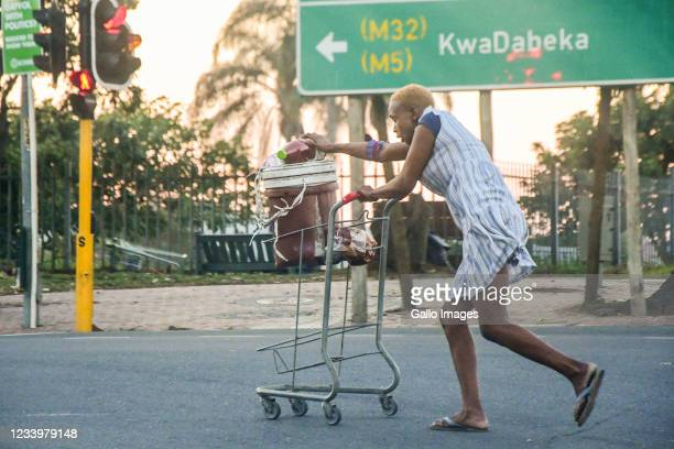 Looter escapes with her loot in Pinetown on July 12, 2021 in Durban, South Africa. It is reported that a considerable number of shops and businesses...