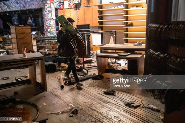 A looter grabs merchandise during a night of protests and vandalism over the death of George Floyd on June 1 2020 in New York City Protesters took to...