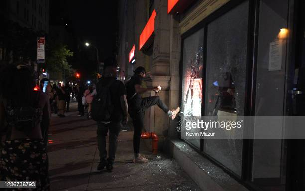 A looter kicks in glass at a Santander bank in Union Square in response to the killing of George Floyd on May 30 2020 in New York City Demonstrations...