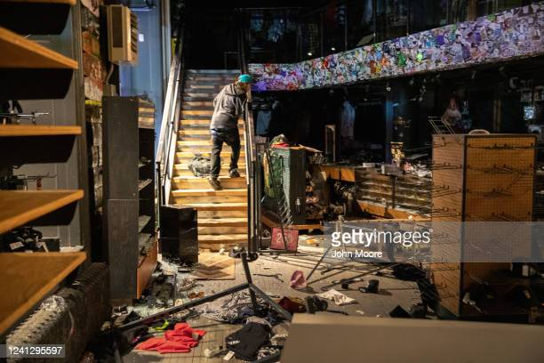 A looter looks for merchandise during a night of protests and vandalism over the death of George Floyd on June 1 2020 in New York City Protesters...