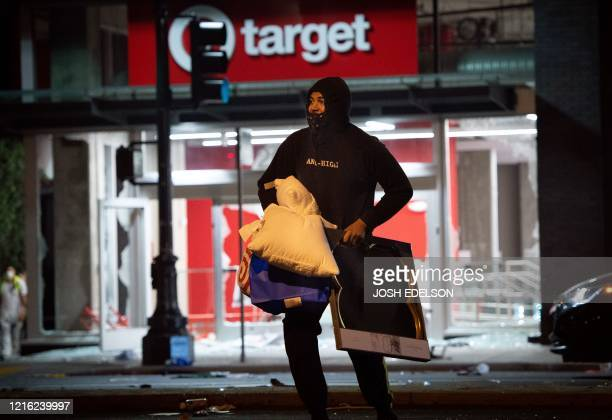 A looter rob a Target store as protesters face off against police in Oakland California on May 30 over the death of George Floyd a black man who died...