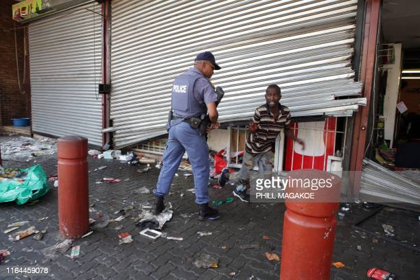 TOPSHOT A looter runs away from a South African Police Service member during a riot by taxi drivers near the Bloed Taxi Rank on August 28 2019 in...