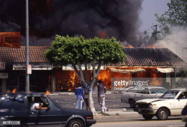 Looters across the street from Viva Shopping center amongst a billowing fire during widespread riots that erupted after the acquittal of 4 LAPD...