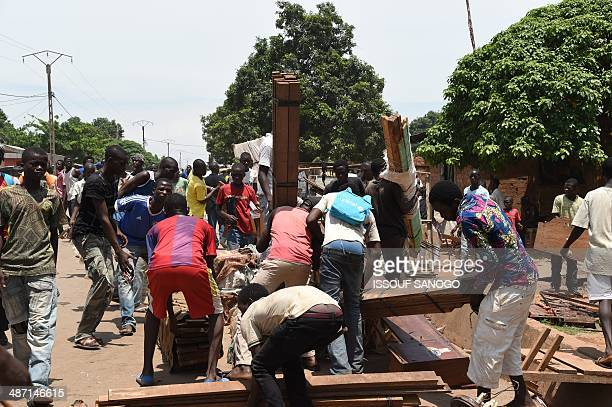 Looters carry pieces of wood from a mosque in the PK12 district as soldiers of Sangaris and MISCA forces look on on April 27 2014 in Bangui after...