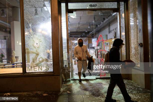Looters emerge from an Urban Outfitters store with merchandise during a riot on May 30 2020 in Seattle Washington A peaceful rally was held earlier...