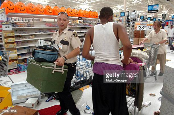 Looters including a unidentified official carry items at a KMart in the Garden District in New Orleans Louisiana on August 30 2005 after Hurricane...