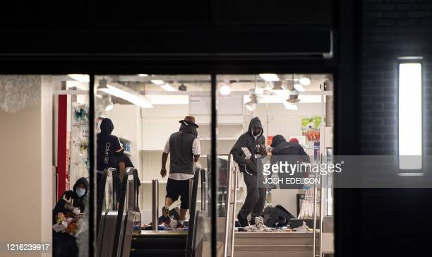 Looters rob a Target store as protesters face off against police in Oakland California on May 30 over the death of George Floyd a black man who died...