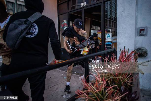 Looters run from a store in Downtown Los Angeles on May 30 2020 during a protest against the death of George Floyd an unarmed black man who died...