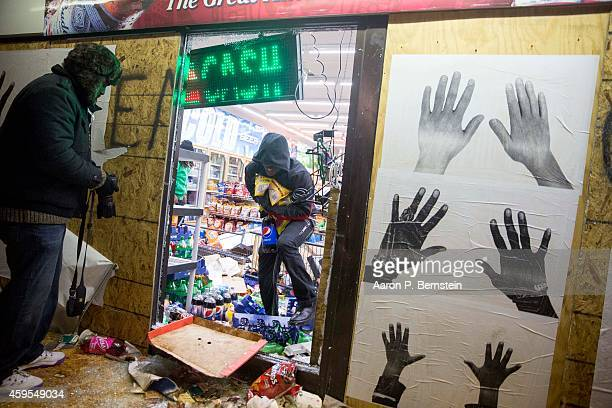 Looters run out of a business during rioting on November 24 2014 in Ferguson Missouri A St Louis County grand jury has declined to indict Ferguson...