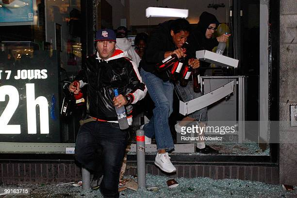 Looters run out of the broken window of a liquor store with bottles of alcohol in downtown Montreal after the Montreal Canadiens defeated the...