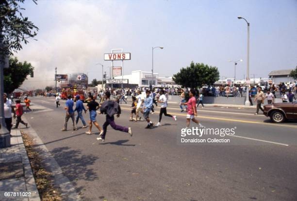 Looters rush across the street from the Vons grocery store at 3461 W. 3rd Street the acquittal of 4 LAPD officers in the videotaped arrest and...