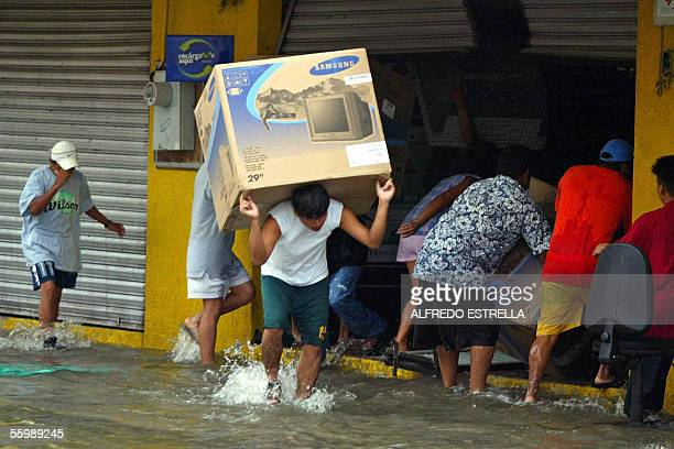 Looters rush with their haul 23 October taking advantage of devastated stores after the city was hit by Hurricane Wilma Although heavy rains had...