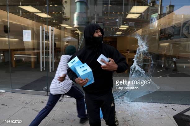 Looters steal from the Appel Store at The Grove as protestors demonstrate at W 3rd St and S Fairfax Ave. In the Fairfax District on Saturday, May 30...