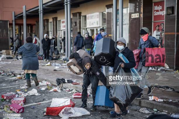 Looters take away few items left to grab in a vandalised mall in Vosloorus, on July 14, 2021. - The raging unrest first erupted last Friday after...